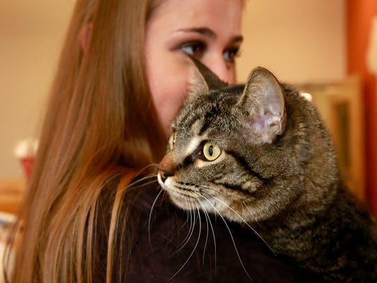 Emma Kinsey holds Pistachio, a domestic short-haired
