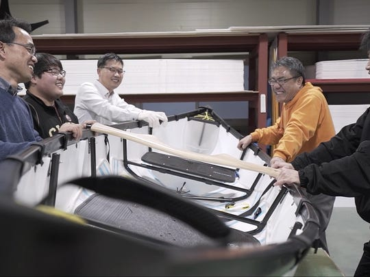 Designers of MyCanoe stand around a prototype.
