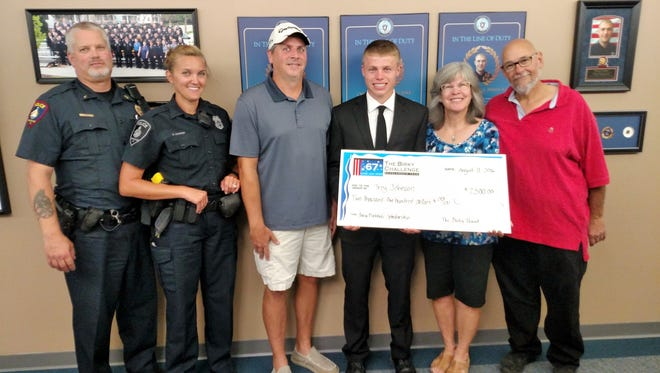 Pictured from left are: Lt. Ed Wenzel, Ofc. Kari Gordee, Joe Braun of the Fond du Lac Area Foundation, Trey Johnson, and Gay and William Birkholz.