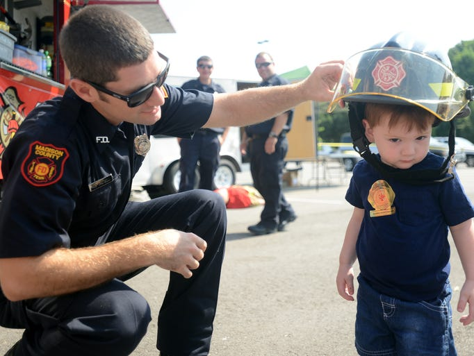 Madison County Fireman Rod Cartrell puts a fireman's helmet on William Hight during a first responders awareness event on Saturday.