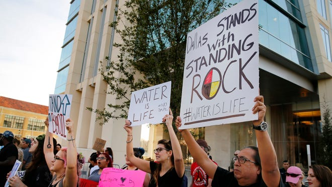 People standing outside developer Energy Transfer Partners headquarters protest the Army Corps of Engineers approval of the final section of the Dakota Access oil pipeline, Tuesday, Feb. 7, 2017.