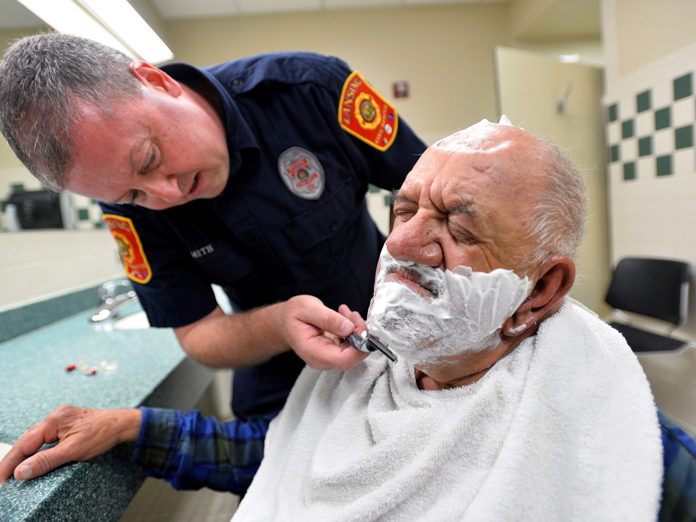 Lansing Fire Department firefighter/paramedic Greg Smith shaves Tony after convincing Tony of the need for it.  Smith and Tumminello share a close bond and constantly joke with each other, with each often telling the other they have been transferred to a closed fire station.