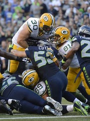 Green Bay Packers fullback John Kuhn (30) leaps into the end zone for a touchdown against the Seattle Seahawks at CenturyLink Field in Seattle, Wash., on Thursday, Sept. 4, 2014.
