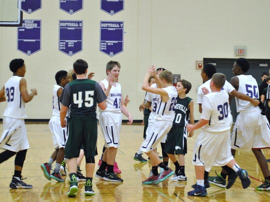 Teammates and opponents surround Walker Fruits (center0 after scoring in a seventh-grade basketball game.