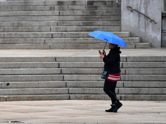 A woman walks past the Bergen County Courthouse in Hackensack on another rainy day in North Jersey on Tuesday, March 28, 2017.