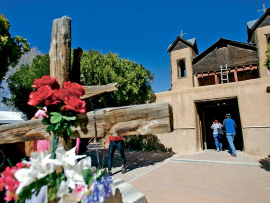 Pilgrims walk into the Santuario de Chimayo on Thursday,