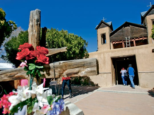 Pilgrims walk into the Santuario de Chimayo on Thursday, March 24, 2016 in Chimayo, N.M. This is the 200th anniversary of the Santuario de Chimayó, New Mexico, a site of holy significance that each year since it was built draws thousands of people, on foot, from across the desert.