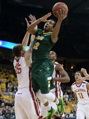 North Dakota State guard Lawrence Alexander drives on Oklahoma forward Tyler Neal. Alexander scored 27 points for the Bison.