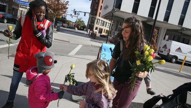 Bridget Strub, of Henrietta, with Tessa, 4, and son Silas, 2, on her back hand out free flowers to Rochester residents Shahama Poole and her three-year-old daughter Laniya near the Liberty Pole.