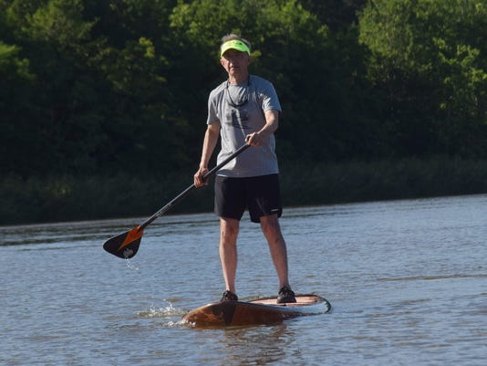Wayne Denley stand up paddle boards on Buhlow Lake in Pineville.