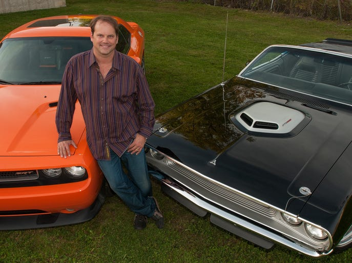 Muscle car enthusiast Brad Ahlgren of Bloomfield Hills poses with two of his Dodge Challengers on Thursday, Sept. 25, 2014. At left is his 2012 Challenger SRT8, which has a 392 Hemi V-8 engine. At right is his 1970 Challenger Convertible with 5-speed manual transmission and a 440 V-8 engine with a shaker hood.