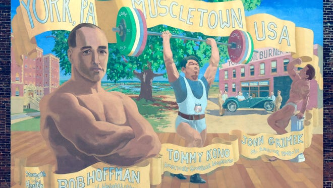 """Monday, May 2, 2016--The """"Muscletown"""" mural depicting weightlifting greats Tommy Kono (center) , Bob Hoffman, left, and John Grimek, is mounted on the building housing Marketview Arts at 37  West Philadelphia St.  Olympic medalist Kono trained at York Barbell during the 1950s when he set several records. He died April 24 in Honolulu. Bill Kalina photo"""