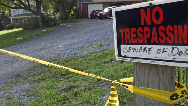 Police tape still remained two days later at the Welsh Run Road property where three people were fatally shot late on June 25, 2016