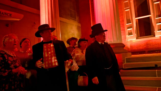 Townspeople look around as buildings are set on fire during the Burning of Chambersburg reenactment.