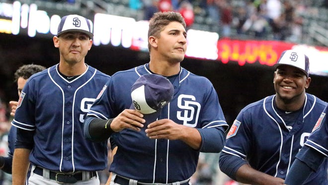 Jose Galindo, left, former Montwood high school pitcher and now San Diego Padres prospect walks to the dugout with other players at the start of the Padres exhibition game with the El Paso Chihuahuas Monday.