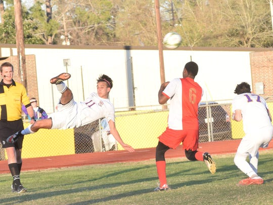 Alexandria Senior High's Slayte Taylor (11, far left) kicks the ball over Helen Cox's Barnal Rene (6, center) and teammate Zachary Walker (17, far right) in the Division II second round Feb. 9.