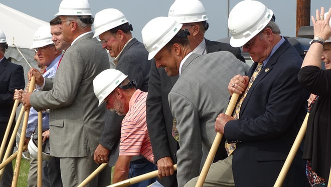 POET Biorefining CEO Jeff Broin, center, smiling, broke ground today on a $120 million project to expand its plant in Marion.