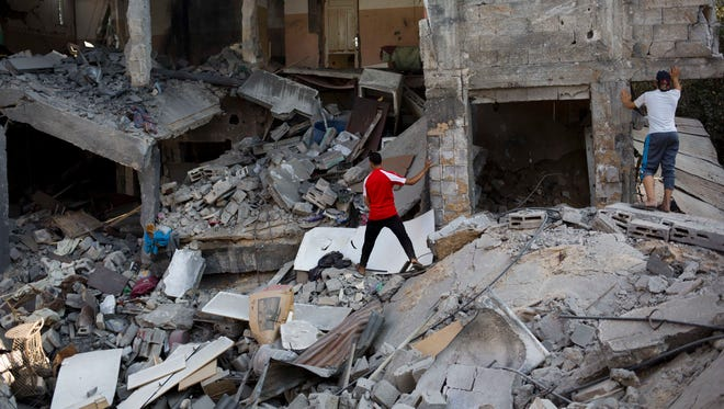 Palestinians inspect a destroyed house in the heavily bombed Gaza City neighborhood of Shijaiyah, close to the Israeli border, on Aug. 1. A Gaza cease-fire that began Friday quickly unraveled as Israel and Hamas accused each other of violating the truce.