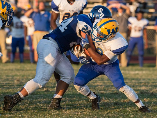 Wi-Hi's Ronnie Satchel (12) attempts to tackle Decatur's Justin Mangianello (24) on Friday, Sept. 8, 2017.