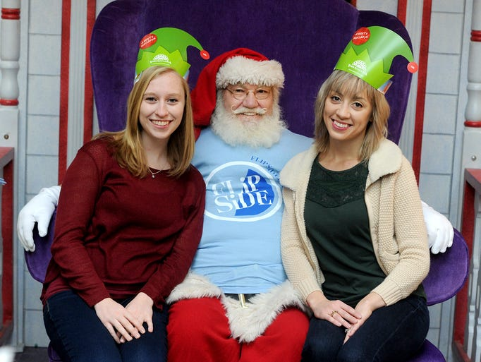 Abbey Zelko, left, and Ashley May pose with Santa at