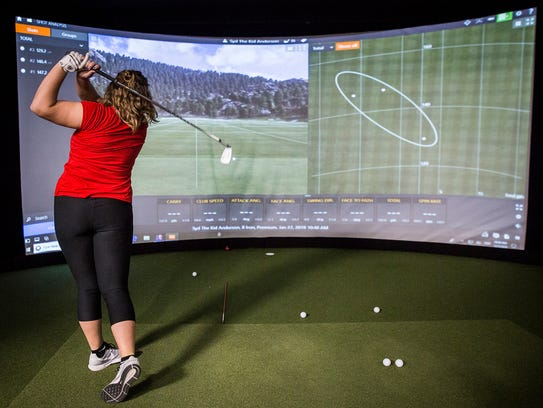 Golfers demonstrate a virtual driving range at the