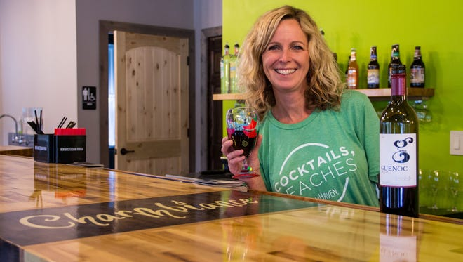 MéShelle leans on the handcrafted bar made out of reclaimed wood that sits in the middle of Charmbiance Art Bar in Hales Corners. It's a place people can come to create and relax, she says.
