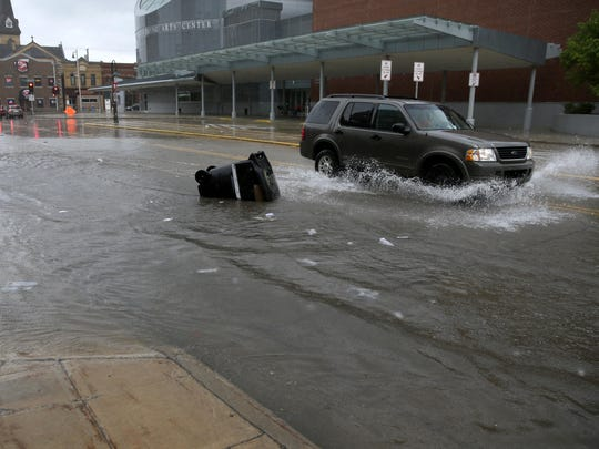 A vehicle drives northbound on a flooded North Division