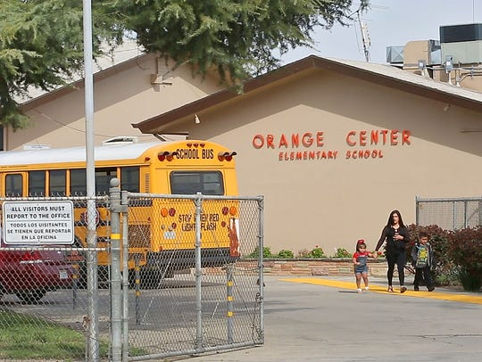 A family leaves Orange Center Elementary School on