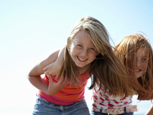 Smiling girls standing together outdoors