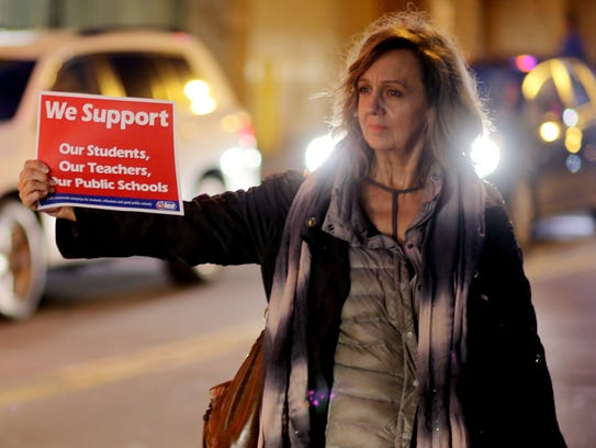 Linda Slobey holds a sign during a protest against