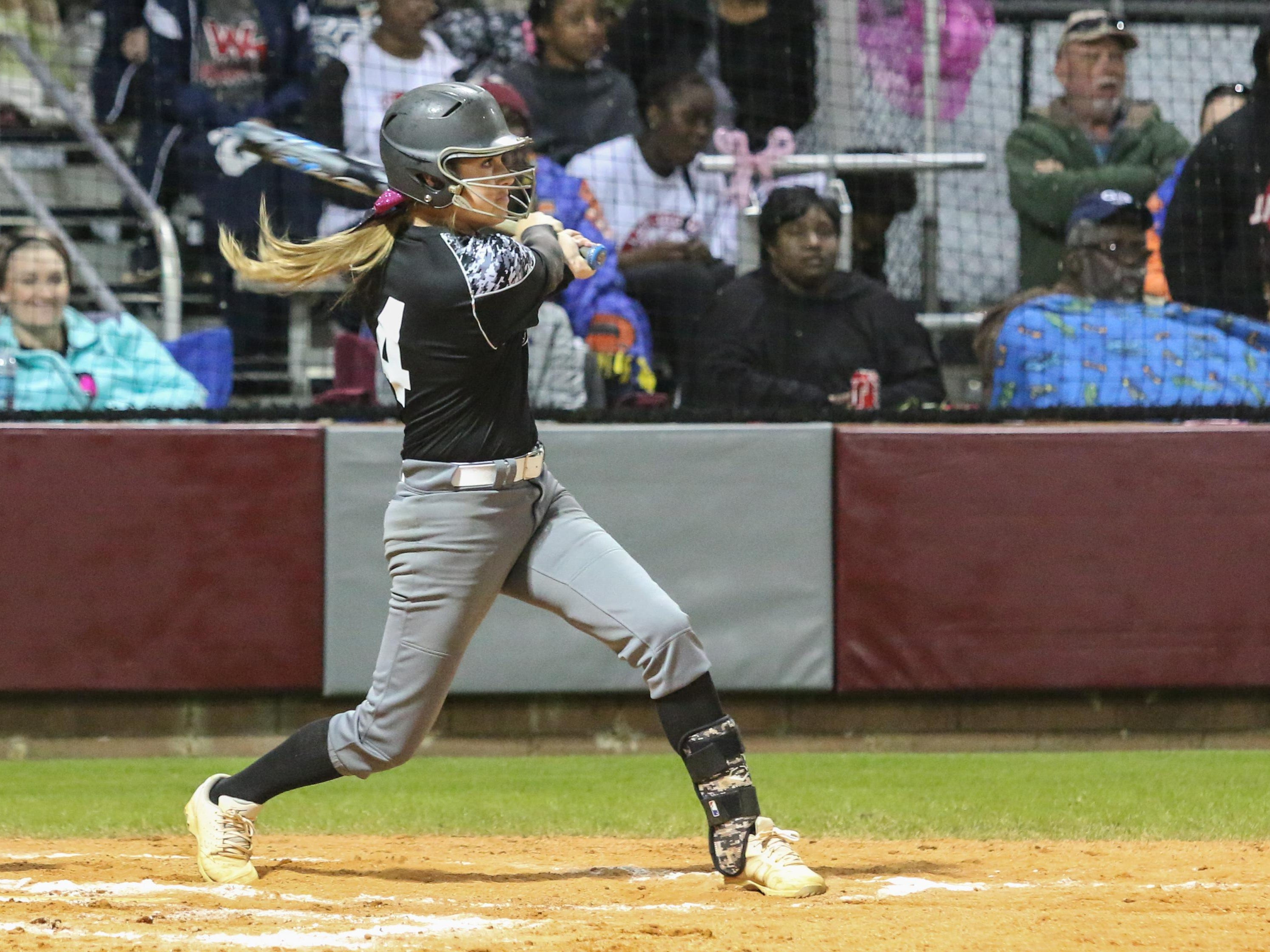 Tate's Savannah Rowell hits the ball Monday night during the 7th Annual Strike Out Cancer benefit softball game at Tate High School. The event helps raise thousands of dollars for the American Cancer Society.