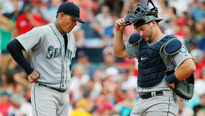 Seattle Mariners starting pitcher Felix Hernandez, left, and catcher Mike Zunino stand on the mound after giving up a run to the Boston Red Sox during the third inning of a baseball game at Fenway Park in Boston Saturday, Aug. 15, 2015.