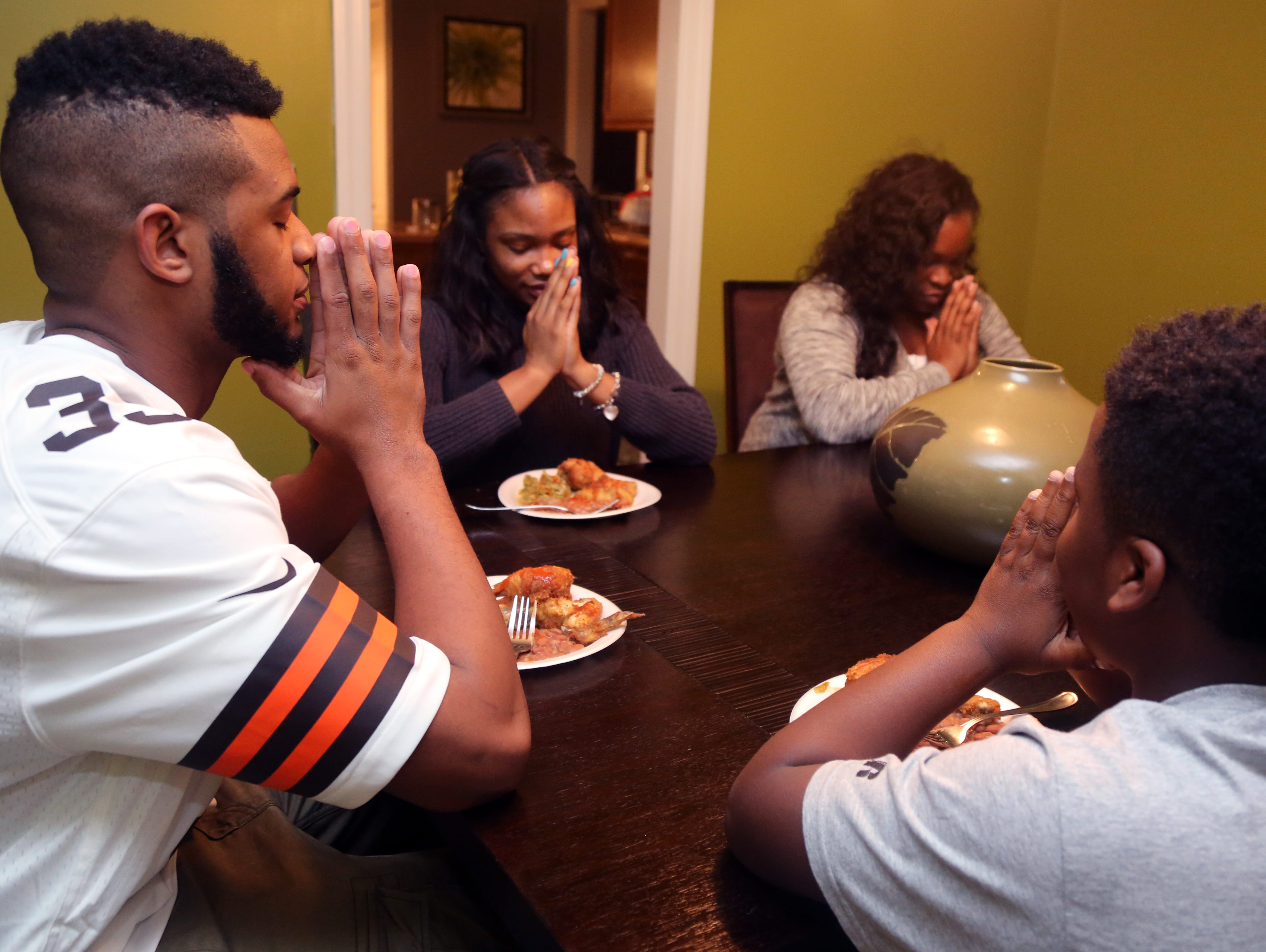 From left to right, Davarius Cortner, Doncoria Cortner, Vanessa Cortner and Kevon Frierson pray before they have dinner on Tuesday, the eve of national signing day.