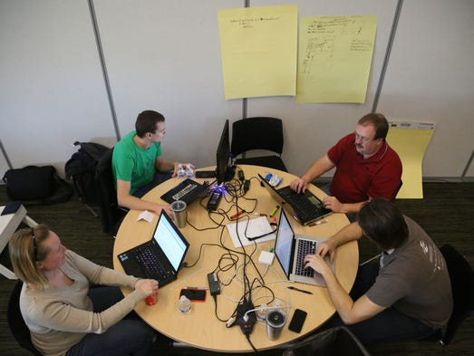 "A group of ""hackers"" from left, Kristin Clemens of Ames, Scot Herren of Des Moines, Darin King of Cedar Falls and Jon Thompson of Des Moines work together at a ""hackathon"" hosted by the New York-based company Dice.com on Saturday, March 15, 2014, at the Future Farmers of America Enrichment Center in Ankeny, Iowa."