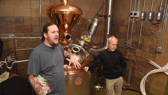 3 Rivers Brewstillery head brewer and distiller Brandon Beard, left, and co-owner Bob Beckley talk about the new business on Nov. 30 while standing next to the still.