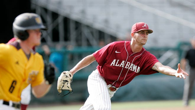 Alabama's pitcher, Taylor Guilbeau tosses over to first to force out Kennesaw State's Jacob Bruce in the third inning of an NCAA regional baseball game on Sunday in Tallahassee, Florida.