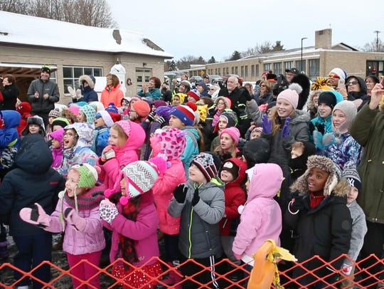 Students from St. Pius X School cheer as workers from