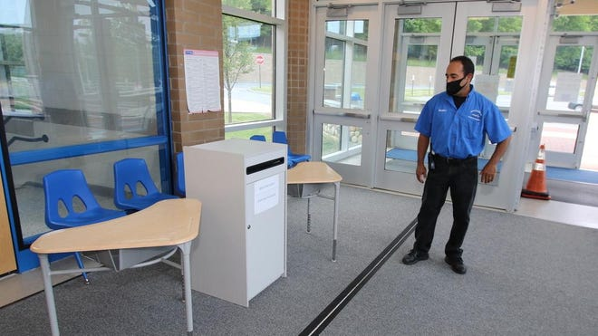 Raul Santos,  security aid for the Middletown School District, talks about how a person is able to walk in and slip the absentee ballot into the locked and secured box in the lobby. He is there during the day so  people can come and safely and securely drop off their ballots.