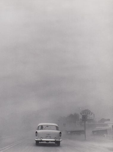 A dust storm obscures the street as a car drives toward