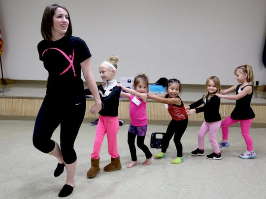 Emily Salter, the dance director, leads students in a warm-up during a Just for Kix dance class at the Scottish Rite Center.