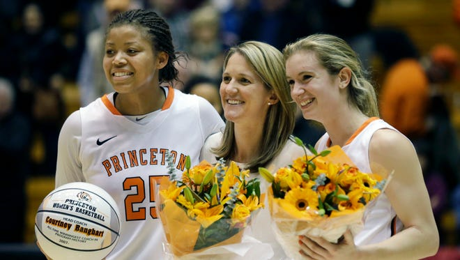 Princeton head coach Courtney Banghart, center,  stands with forward Mariah Smith, left,  and Blake Dietrick, right, after an NCAA college basketball game against Yale Friday, Feb. 27, 2015, in Princeton, N.J. Princeton won 67-49. With the win, Banghart became the winningest coach in women's basketball at Princeton.