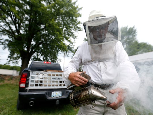 Beekeeper Michael Myer sprays himself with smoke before