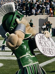 "MSU Mascot Sparty holds a sign asking, ""What the heck's"