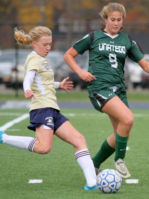 Notre Dame's Allegra Dawes goes to kick the ball as Unatego's Cassidy Newman defends during a Section 4 Class C girls soccer semifinal at Notre Dame on Wednesday.