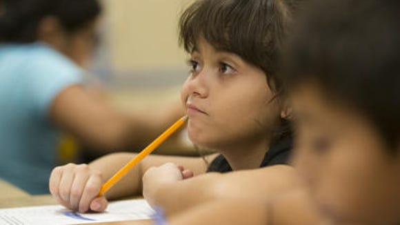 Lehi Elementary second grade student Heyddy Ramos pauses while writing about what she did over the summer during the first day of school in Mesa August 6, 2014.