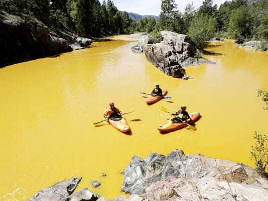 FILE - In this Thursday, Aug. 6, 2015 file photo, people kayak in the Animas River near Durango, Colo., in water colored yellow from a mine waste spill. (Jerry McBride/The Durango Herald via AP, FILE)