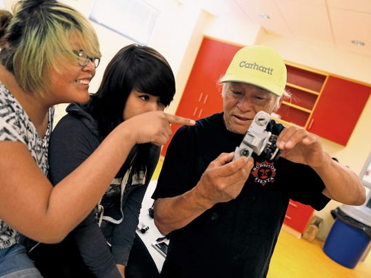 Sam Minkler, right, an associate professor at Northern Arizona University, teaches a group of students about cameras and aperture Tuesday during a multimedia media workshop put on by Paper Rocket Productions at the Shiprock Youth Complex.