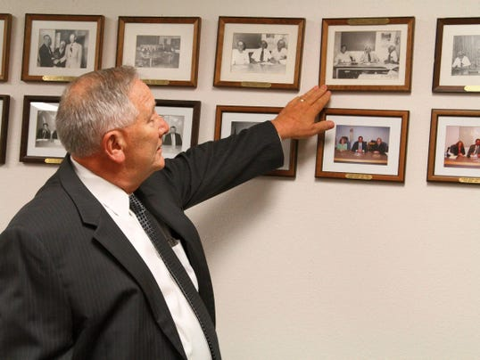 Duane Barbati — Daily News Otero County attorney Daniel A. Bryant looks at pictures of former commissioners that he has worked with over the years. Bryant was appointed by Gov. Susana Martinez to the 12th Judicial District Court judge's seat in Carrizozo Friday.