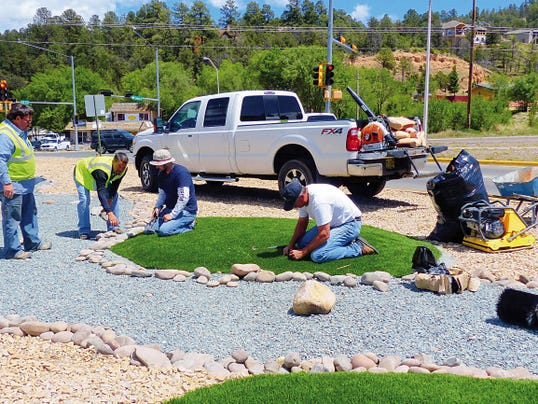 Rodney Griego, director of the Ruidoso Parks and Recreation Department, second from right, helps a Southwest Greens crew, at right, with the finishing touches for the revamped landscaping at the intersection of U.S. 70 and NM 48. Work began two weeks ago with a street department crew scraping and rolling out the area in preparation for the rock work, then David Tetreault and members of EcoServants laid the weed barrier.