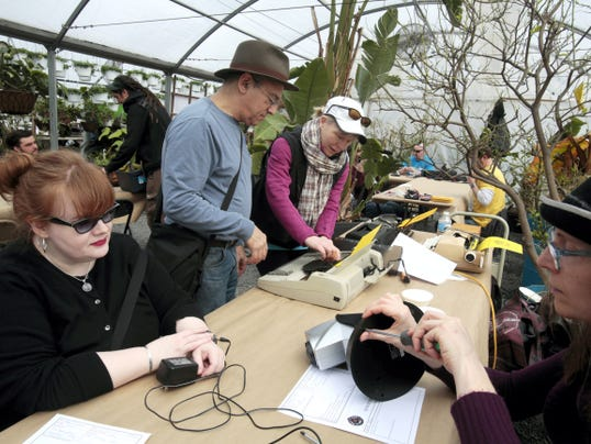 """In this March 28, 2015 photo, Fixer Fran Blanche, right foreground, examines Kathy Kruger's broken laser star projector at the Repair Fair at Greensgrow in Philadelphia. Volunteer """"fixers"""" in Philadelphia have started offering their skills for free in an effort to promote resourcefulness and sustainability, and to help build a sense of community. Fixer Bryan Kravitz, center background, helps Dianna Collins with a typewriter repair. (AP Photo/Jacqueline Larma)"""